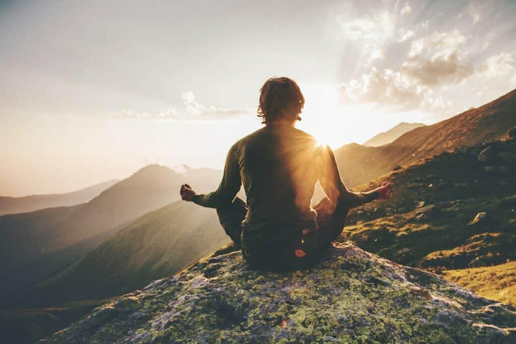 homme en éveil spirituel grâce à la méditation en montagne